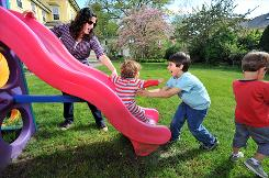 Jodie Casagrande, a stay-at-home mom, plays with her three sons, Roman, 18 months, Lucca, 6, and Matteo, 3, right, in their backyard in Jamaica Plain, Mass.