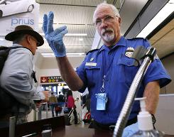 TSA officer Robert Howard signals an airline passenger forward at a security check-point at Seattle-Tacoma International Airport on Jan. 4. Rules concerning the no-fly list are being tightened in the aftermath of the recent Times Square attempted bombing.