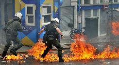 Greek riot police clash with protesters in the center of Athens on Wednesday during a a nationwide anti-austerity strike. Three people were killed in a firebomb attack on a bank in the center of Athens.