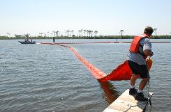 The Naval Air Station Pensacola pollution response unit deploys an oil containment boom at Sherman Cove in Pensacola, Fla., to protect grass beds from the oil spill in the Gulf. Low winds continued to keep most of the oil away from shore Wednesday.