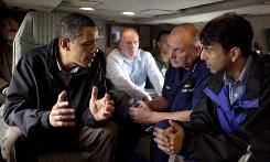 President Obama talks with Louisiana Gov. Bobby Jindal, right, and U.S. Coast Guard Commandant Adm. Thad Allen on Marine One as they fly along the Louisiana coastline Sunday.