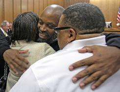 Raymond Towler, center, hugs his sister Debbie Settles, left, and his brother Clarance Settles after being released from prison Wednesday.
