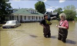 Nashville resident Emerson Eubank tells his neighbor, Pam Hiers, what he saw when he waded through floodwaters Wednesday to check out the damage to their homes.