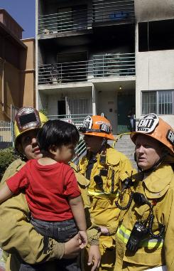 A firefighter holds a child as his mother stands nearby after a Saturday fire at an apartment building near downtown Los Angeles injured 13 people.