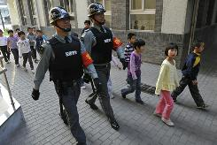 Security guards in bullet-proof vests and armed with batons and Tasers guard an elementary school in Beijing on Thursday.