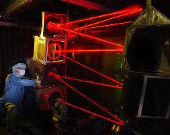 "An engineer adjusts a mirror in the ""wall of fire,"" a zigzag-shaped optical path used by the Airborne Laser Test Bed's missile-killing high energy laser, during a test at the Lockheed Martin facility in Sunnyvale, Calif., in 2003. The ""wall of fire"" was part of the 6,100-pound beam transfer assembly, installed in the Airborne Laser Test Bed aircraft at Edwards Air Force Base, Calif."