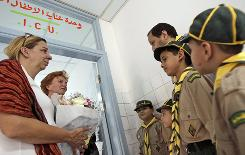 A woman, left, identified by Dutch foreign ministry staff as the aunt of Ruben van Assouw, sole survivor of the Afriqiyah Airways Flight 771 plane crash, holds a bunch of flowers she just received from a delegation of young Libyan boy scouts.
