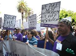 Larry Hill, right, a health care worker from Los Angeles, joins dozens  of other health care workers and supporters in a protest outside the Secretary of State's office where Gov. Arnold Schwarzenegger unveiled his revised 2010-2011 state budget in Sacramento.