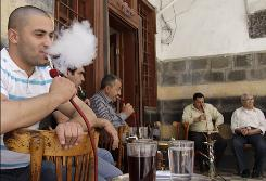 Syrians smoke water pipes outside a cafe in Damascus after a ban on smoking in most public places went into effect.