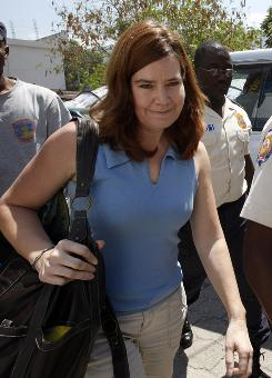 U.S. missionary Laura Silsby, 40, of Meridian, Idaho, is escorted by police officers upon her arrival to the courthouse in Port-au-Prince, Haiti.