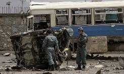 Afghan policemen look at the mangled remains of a vehicle after a suicide attack in Kabul on Tuesday.