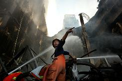A firefighter works to control a blaze at the Central World shopping mall in Bangkok on Thursday.