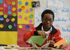 Tanya Douglas, 22, a tutor and mentor in AmeriCorps' City Year program, puts together bags of candy for students celebrating recent birthdays at Feltonville School of Arts and Sciences in Philadelphia.