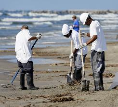 Workers collect oil and debris that washed up onto a beach in Grand Isle, La., Saturday.