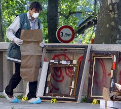 Police officers search for clues as they pack up the frames of the stolen paintings outside the Paris Museum of Modern Art, following the report of five paintings having been stolen, Thursday.