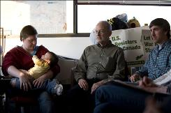 "Iraq war deserter Kimberly Rivera, with one of her children, attends a war resisters support meeting in Toronto with Charlie Diamond, center, a Vietnam War objector and Phil McDowell, who went AWOL after being ordered back to Iraq under the Army's ""stop-loss"" policy."
