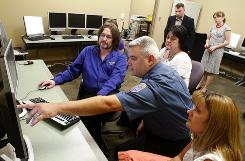 Merrille Noe, left, instructs fellow EMS staff member Rick Roller in Louisville's program to reduce ambulance runs and ER crowding, as Amy Pierce, right and Kim Wright watch.