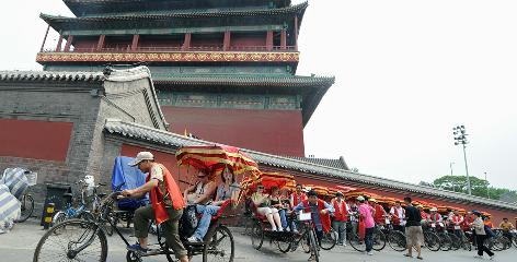 A pedicab driver leads a convoy of travelers touring Beijing's Drum and Bell Tower neighborhood.
