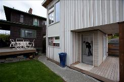 John Stoeck sweeps the 437-square-foot cottage he's building behind his home in Seattle. The city changed zoning rules to allow cottages in single-family neighborhoods.