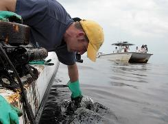Kevin Boswell, a Louisiana State University researcher, skims some oil from the surface of Gulf waters.