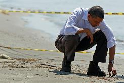 President Obama picks up balls of tar Friday while touring the beach in Port Fourchon, La.