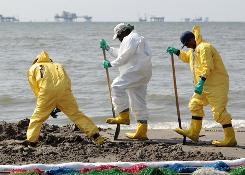 Workers clean up oil residue along the beach in Port Fourchon, La., Saturday.