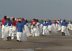 Workers walk along the beach as they clean up oil residue in Grand Isle, La., Sunday.