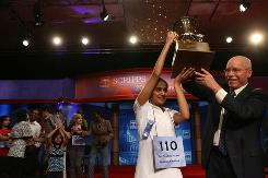 Kavya Shivashankar holds the trophy after winning the 2009 Scripps National Spelling Bee in Washington, May 28, 2009. Behind her, hands lifted in applause, is her sister Vanya. This year, Vanya, 8, will be the youngest spelling bee entrant.