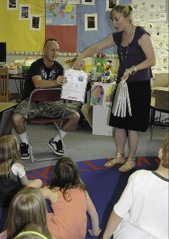 In Arvada, Colo., Fitzmorris Elementary kindergarten teacher Kat Krisher hands parent Wade Walton a packet of books for his child to read over the summer.