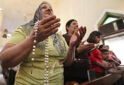 Iraqi Christians pray at Virgin Mary Church in Baghdad on April 4. Their community has been a target of violence.