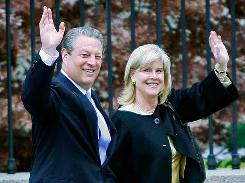 Former vice president Al Gore and his wife Tipper Gore wave as they walk down a sidewalk at the White House after posing for photos with then-President George W. Bush and other Nobel Prize winners in 2007.