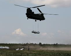 Members of the Louisiana National Guard stand by after hooking up sandbags to helicopters for deployment against the Deepwater Horizon oil spill in Buras, La., on Tuesday.