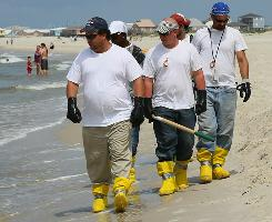 Contract workers patrol the beach Wednesday on Dauphin Island, Ala., to pick up oil that has washed ashore.
