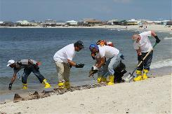 Contracted workers clean up along the beach Tuesday on Dauphin Island in Alabama, where oil has started to wash ashore.