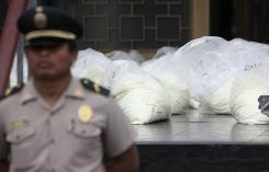 A police officer stands guard by bags of cocaine -- more than four tons were seized around Peru -- in Lima, May 7. Almost 80% of cocaine coming into the USA includes levamisole, an anti-worming agent used in barnyard animals, says epidemiologist Ghinwa Dumyati.