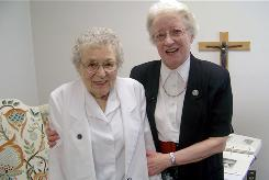 Sister Mary David Olheiser, 92, right, and her friend Sister Helenette Baltes, 94, stand together at St. Scholastica, an assisted living center for Benedictine nuns in St. Cloud, Minn.
