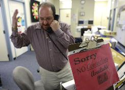 "Head counselor Allen Roberts gestures on the phone at Silver Creek High School in San Jose, Calif., next to a sign that reads: ""Sorry, NO Counselors Available."""