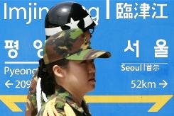 South Korean soldiers walk by a directional sign showing distances to the two Koreas' capitals at a railway station near the demilitarized zone.