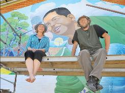 "Mural Mice artists Pamela J. Smith and R.E. Wall sit in front of the Miller Valley School Mural titled "" Go on Green"" in Prescott, Ariz."