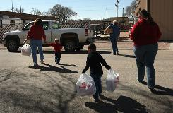 "A family with young boys carries donated food from a food bank truck aid distribution site in Hugo, Colo., in March 2009. This year, 750,000 more children than in 2007 live in families with an ""insecure"" source of food, according to a non-profit's analysis."