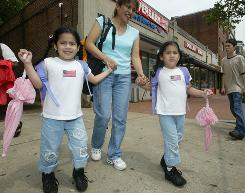 Minorities, such as Hispanic twins Michelle, left, and Melanie Pisqui-Beltran, 5, and mom Gina Beltran in Washington, made up more than half the population in 317 counties, four states and D.C., according to Census estimates July 1, 2009.