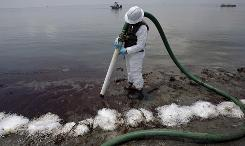 A worker uses a suction hose Wednesday to remove oil washed ashore from the Deepwater Horizon spill in Belle Terre, La.