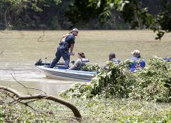 Officials search near the edge of the Little Missouri River near Langley, Ark., on Saturday after a flash flood swept through a popular campground.