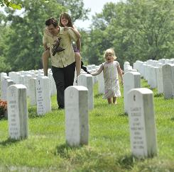 Scott Adams, 46, carries his daughter Alyssa Adams, 13, followed by his niece Charlotte Akers, 3, as he and other family members visit his father's grave site in the mishandled Section 66 of Arlington National Cemetery in Northern Virginia.