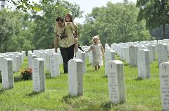 Scott Adams, 46, carries his daughter Alyssa Adams, 13, followed by his niece Charlotte Akers, 3, as he and other family members visit his father's grave site in Section 66 of Arlington National Cemetery in Northern Virginia.