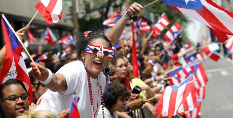 Puerto Rican flags wave as spectators line Fifth Avenue during the Puerto Rican Day Parade on Sunday in New York City. The party celebrates the heritage of almost 800,000 New Yorkers.
