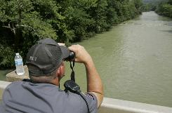A Pike County deputy searches the Little Missouri River near Caddo Gap, Ark., on Saturday.