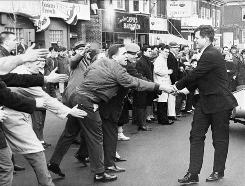 Campaigning for the U.S. Senate in Boston on March 17, 1962, Edward Kennedy greets the crowd at a St. Patrick's Day parade. He received death threats throughout most of his political career.