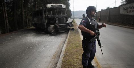A Mexican police officer stands near the area where federal agents were ambushed Monday in Zitacuaro. Authorities believe gunmen used the burning bus to block the road during the attack.