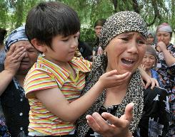 Ethnic Uzbek women cry in a village of Nariman outside Osh at the Kyrgyz-Uzbek border on Tuesday. The first humanitarian aid arrived for tens of thousands who fled deadly ethnic bloodshed in Kyrgyzstan.